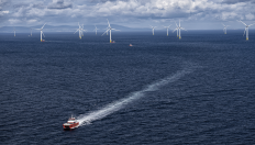 Image shows an offshore wind farm with a boat