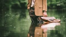 business man with a briefcase standing up to his knees in water