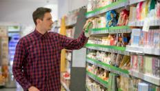 Man in supermarket looking at crisp packet