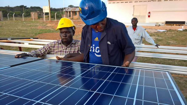 Africa man inspecting a solar panel