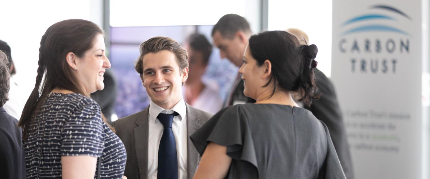 Three people at an event, chatting.