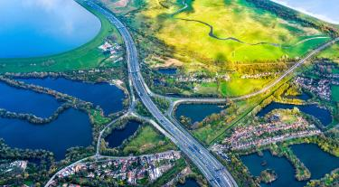 A road and roundabout seen from above, cutting through sunlit green fields and flooded plains