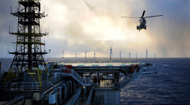 Image shows a helicopter flying above an offshore station with offshore wind turbines in the background