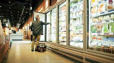 Man looking in a supermarket fridge
