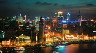view of buildings across a river in China at night