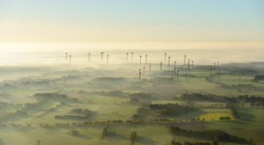 Landscape at sunrise and fog with wind turbines