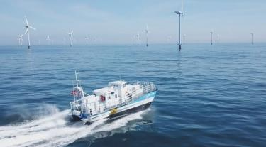 sea puffin vessel boat in the ocean heading towards offshore wind turbines