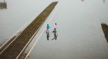 two children play in a flood on a road