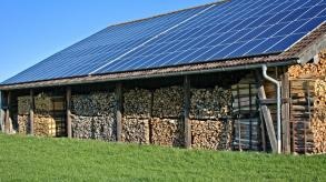 solar panels on roof of large wood shed
