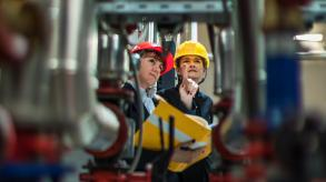 two people in hard hats looking up at equipment