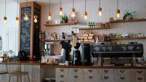 coffee shop counter featuring plants and hanging lights
