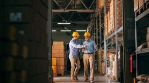 Two men wearing hard hats in a warehouse